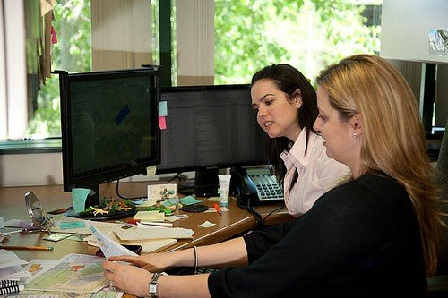 Photo of two women looking at a printed map while sitting at a desk.