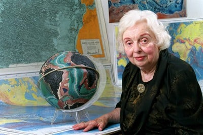 Maria Tharp in 2001 with a globe of the ocean floor.  Photo by Bruce Gilbert.